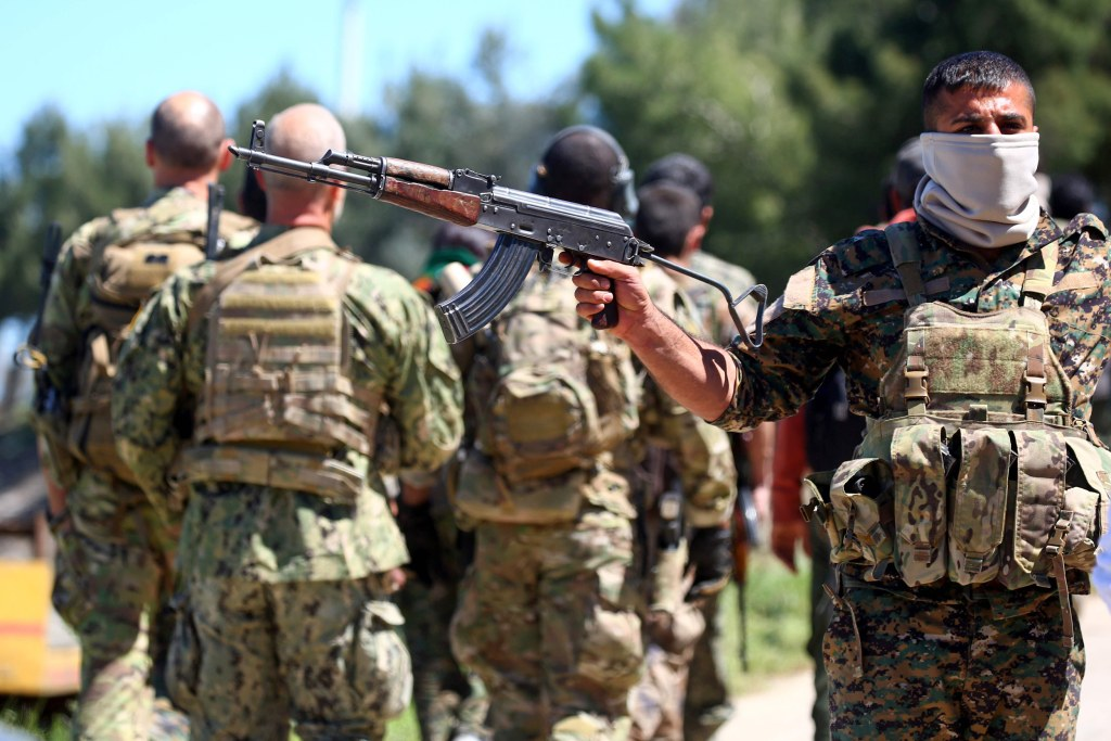 Image: Fighters from the Kurdish People's Protection Units (YPG) stand guard at the site of Turkish airstrikes