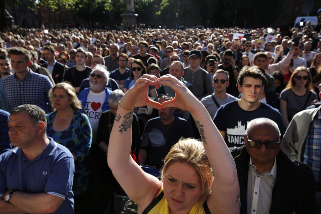 Image: A woman makes a heart gesture as crowds gather