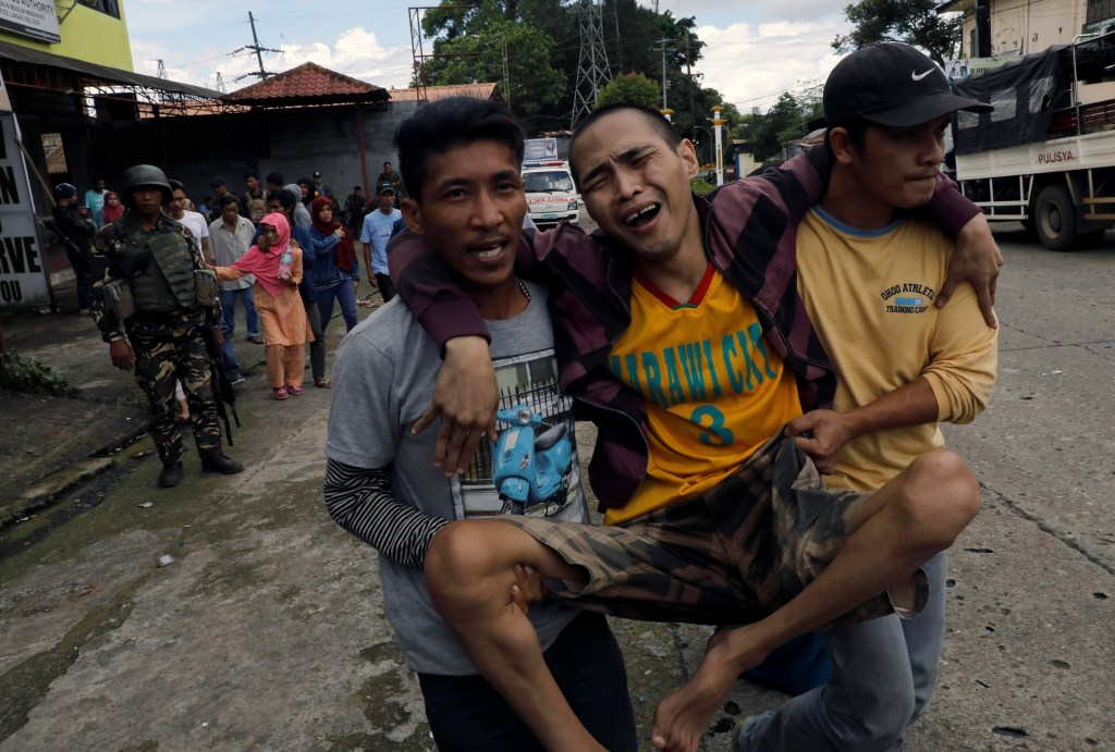 Image: A displaced resident is helped from Marawi City, Philippines.