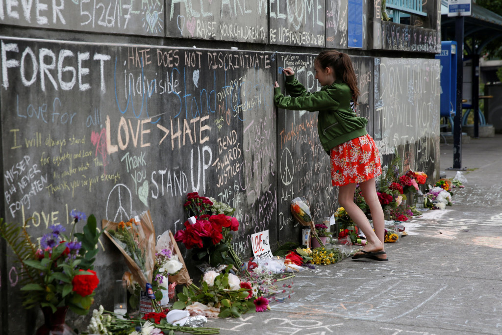 Image: A girl leaves a message at a makeshift memorial for two men who were killed on a commuter train while trying to stop another man from harassing two young women who appeared to be Muslim, in Portland