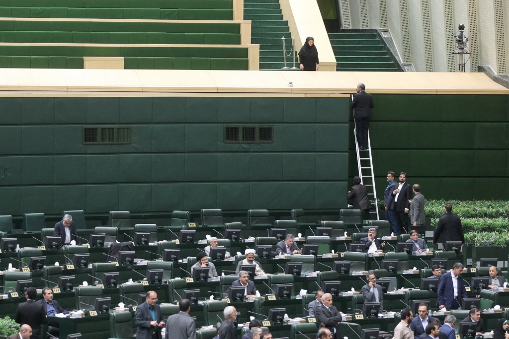 Image: Iranian lawmakers sit inside the parliament during an attack in central Tehran