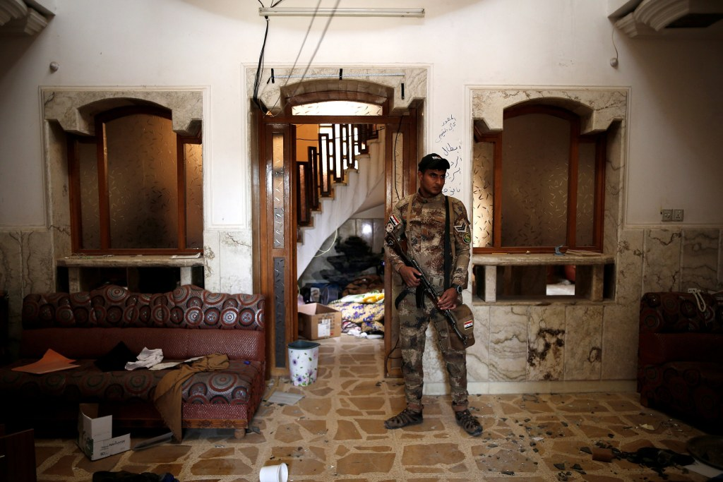Image: An Iraqi soldier stands inside a compound ISIS used as a prison