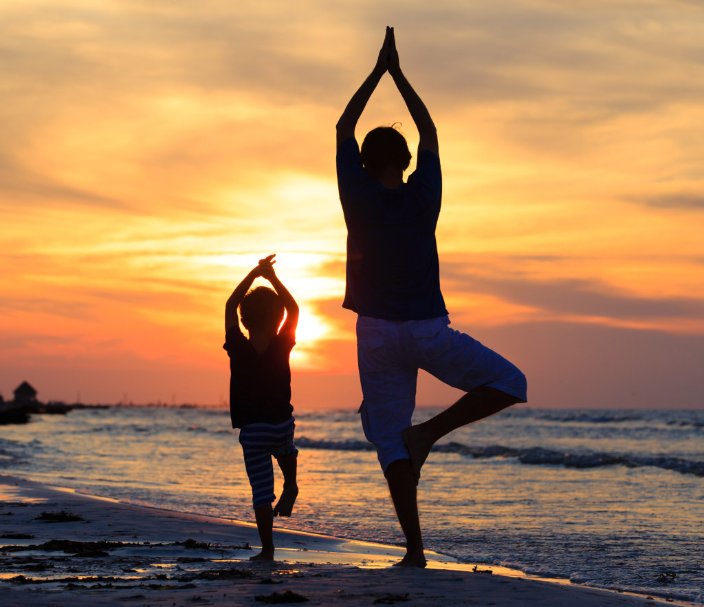 Image: Father and son practice yoga together at sunset