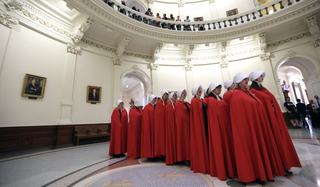 Image: Activists dressed as characters from The Handmaid's Tale chant in the Texas Capitol Rotunda