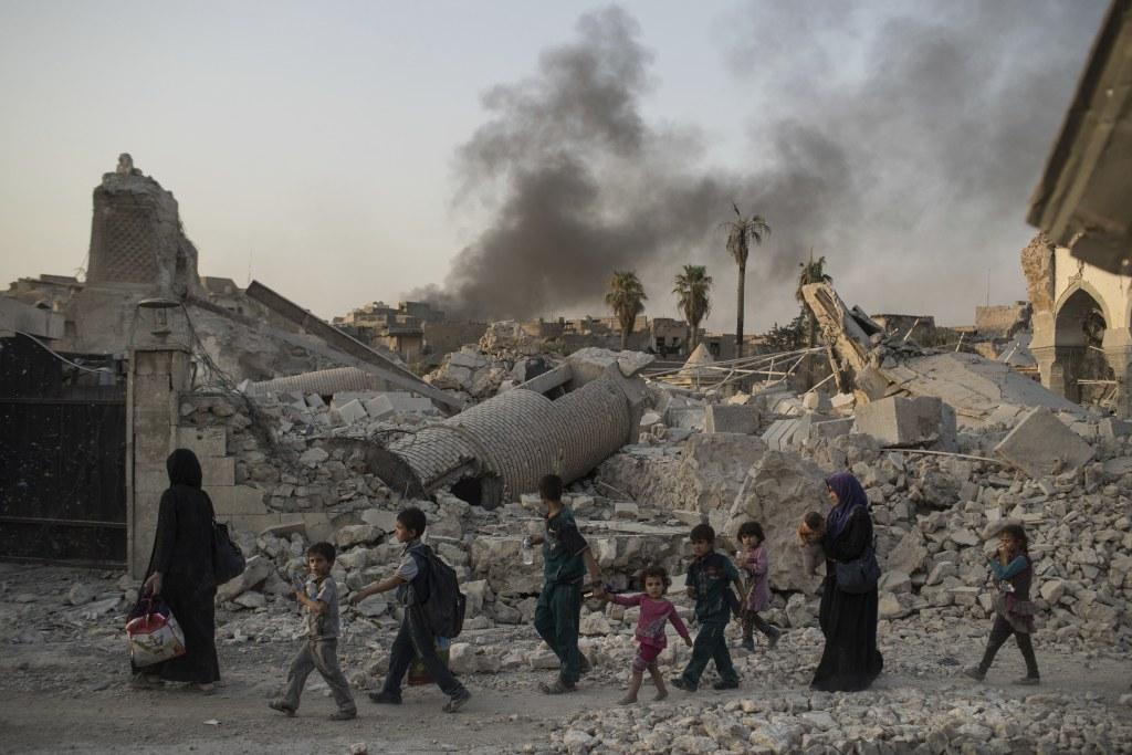 Image: Fleeing civilians walk past Mosul's heavily-damaged al-Nuri mosque during Iraq's war on ISIS