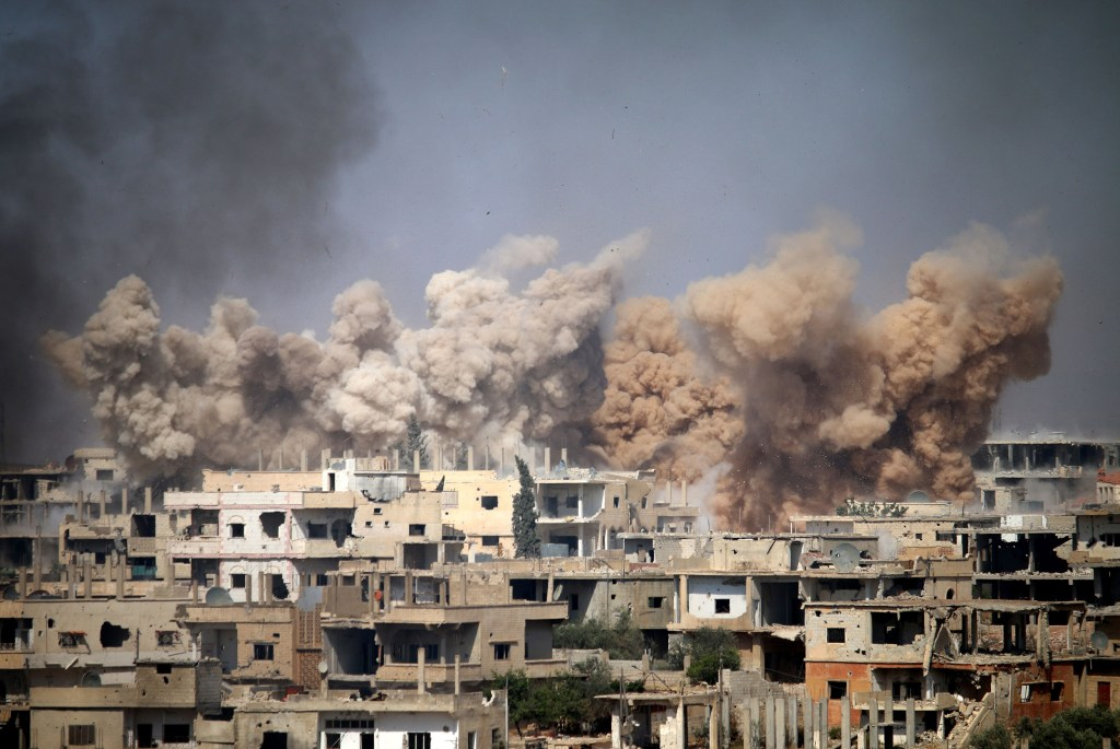 Image: Smoke rises from buildings following a reported air strike on a rebel-held area in the southern Syrian city of Daraa