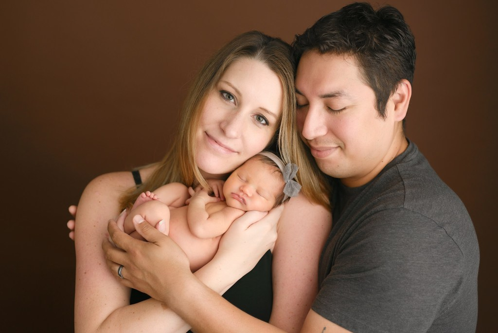 Image: Michelle Zavala poses with her husband and newborn baby