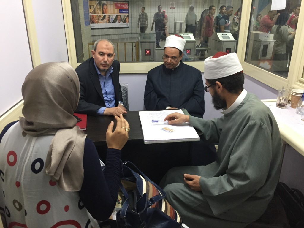 Image: Muslim clerics huddle with passengers at a table in a windowed kiosk