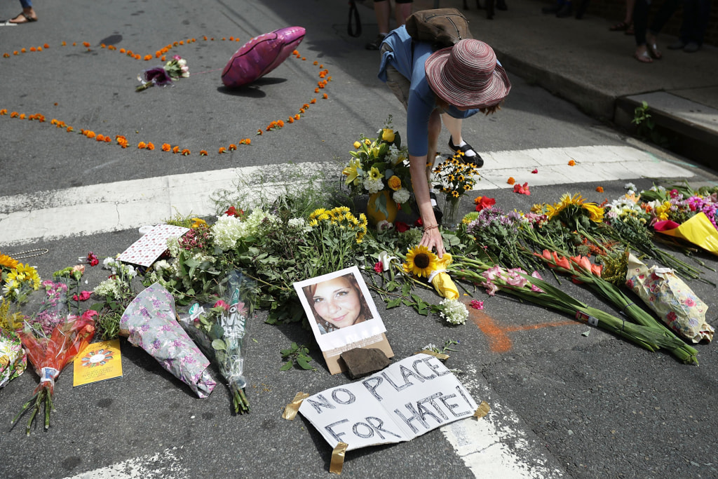 Image: A woman places flowers at an informal memorial to 32-year-old Heather Heyer