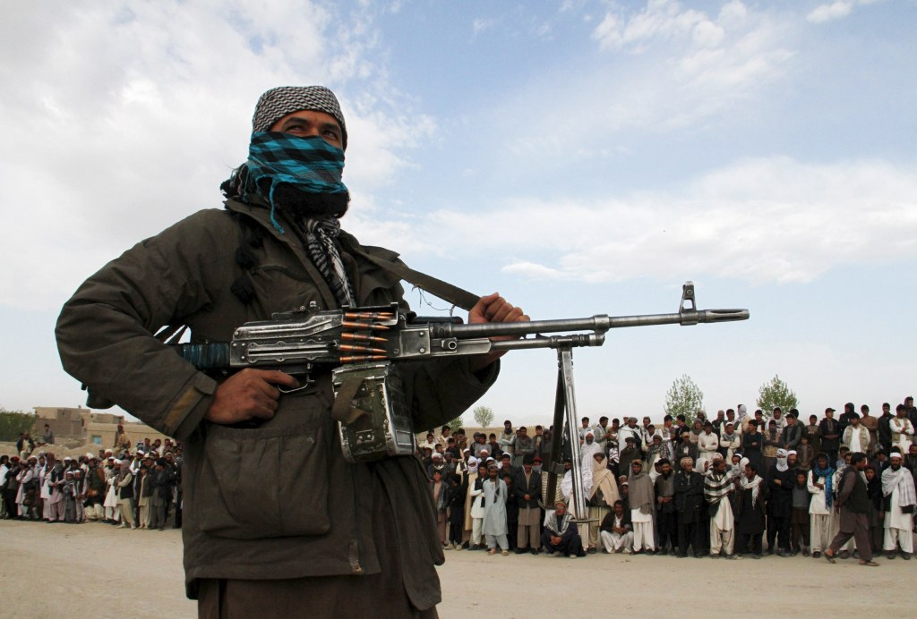 Image: A member of the Taliban insurgent and other people stand at the site during the execution of three men in Ghazni Province