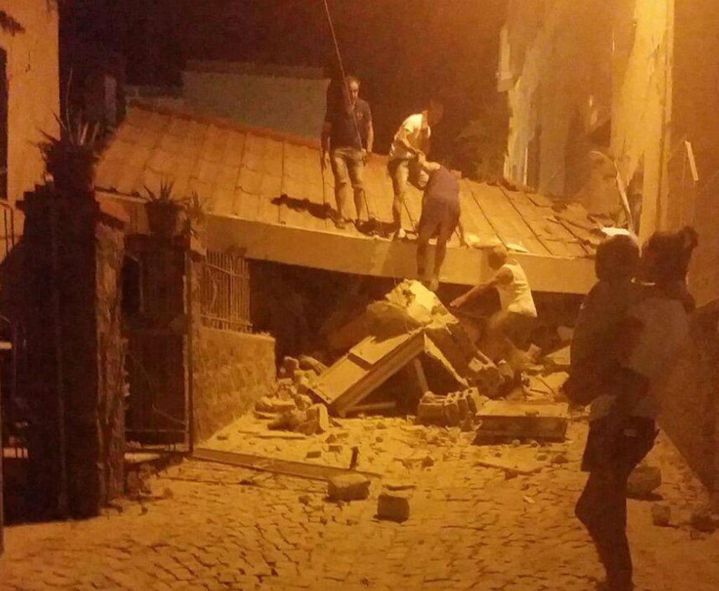 Image: People remove debris after an earthquake hit the island of Ischia, near Naples, Italy