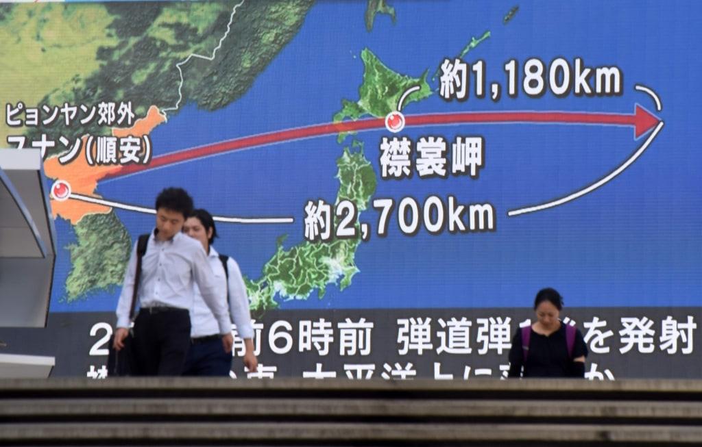 Image: Pedestrians in Tokyo walk past screen showing map of Japan and Korean Peninsula