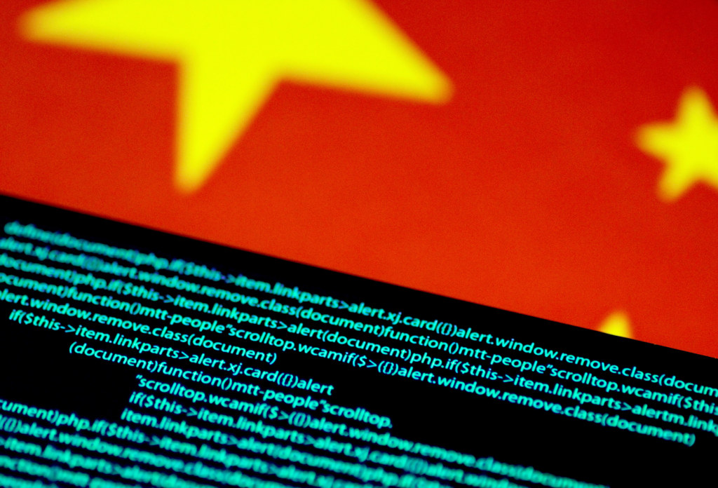 Image: Computer code is seen on a screen above a Chinese flag