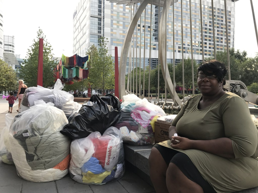 Image: Quajhonita Martin, 31, sits outside the George R. Brown convention center in downtown Houston with her belongings packed to stay with a relative until she can find a job, Sept. 1, 2017.