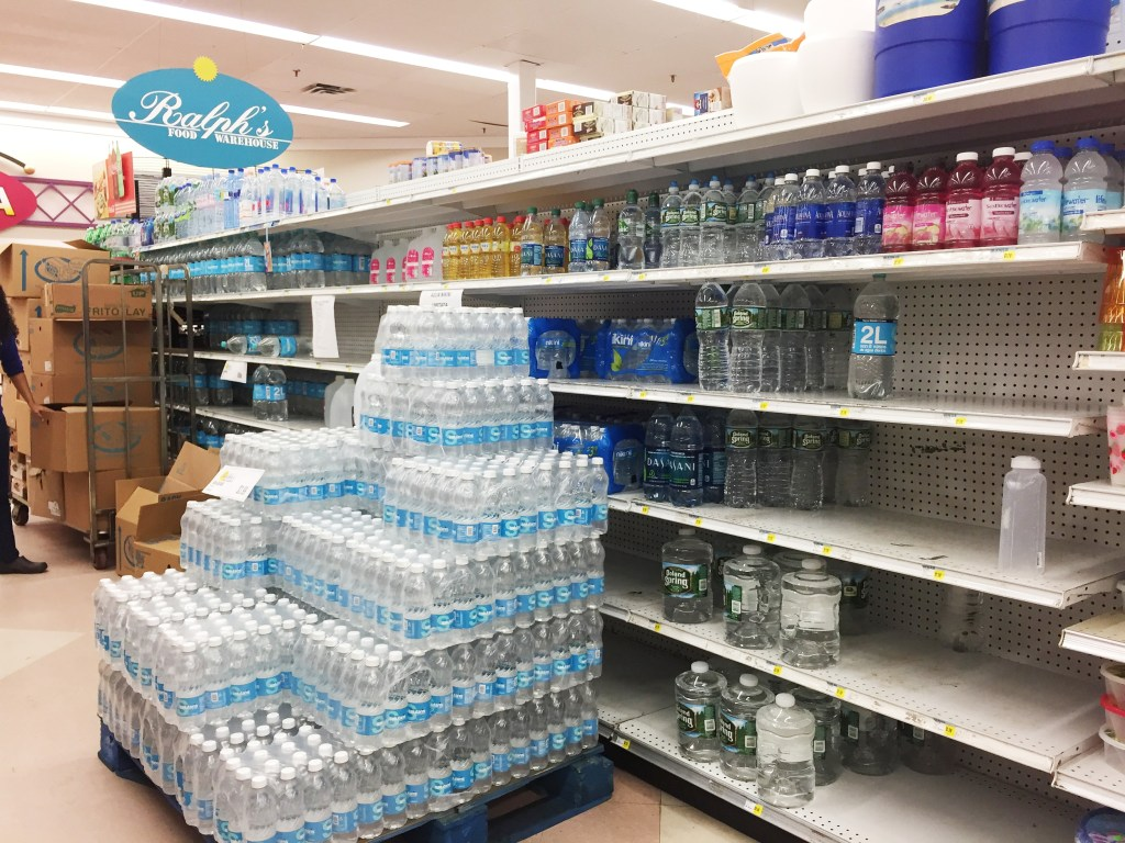Image: Water bottles have been placed in front of partially empty shelves at Ralph's Supermarket in Gurabo, Costa Rica