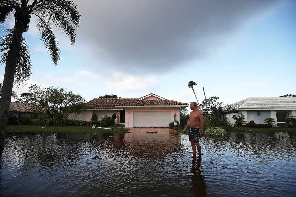 Image:  Jerry Darnell stands in front of his house that was flooded by Hurricane Irma