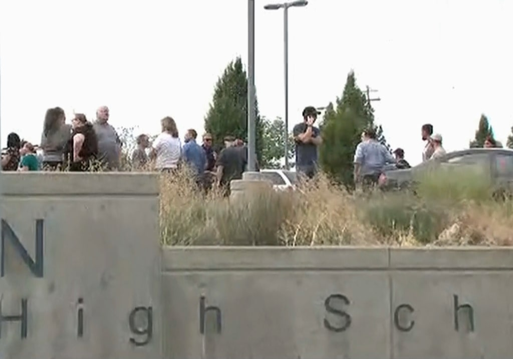 Image: People including parents stand outside Freeman High School in Spokane, Washington