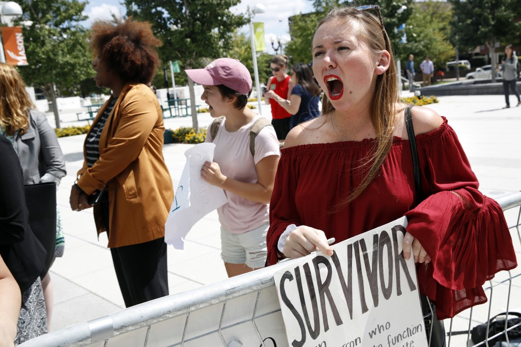 Image: Meghan Downey, 22, a recent graduate from the College of William & Mary, reacts outside an auditorium after Education Secretary Betsy DeVos spoke