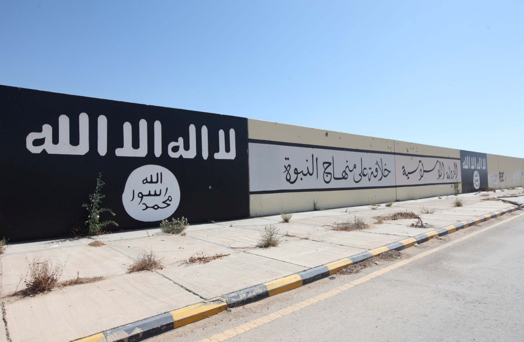 Image: ISIS flags and slogans cover a wall in Sirte in 2016
