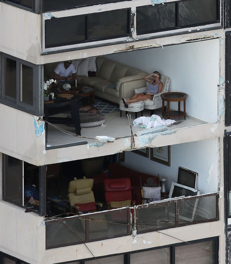 Image: People sit in their apartment with the window blown out in San Juan