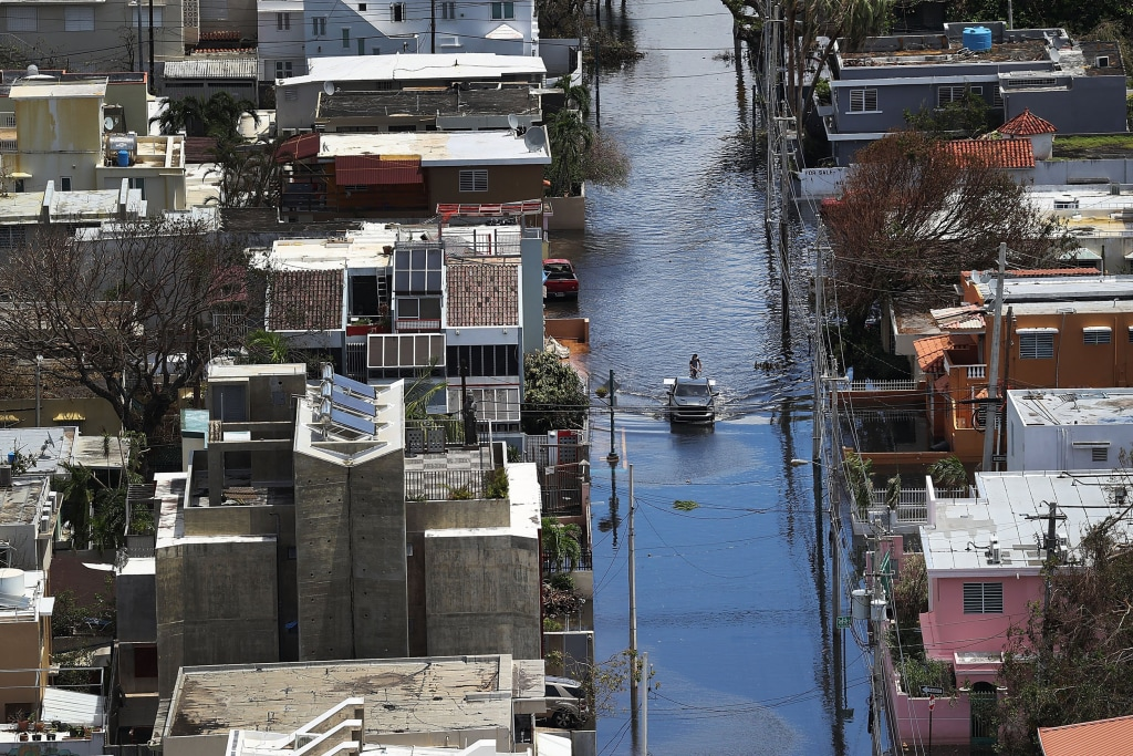 Image: A man stands on a car on a  flooded street in the aftermath of Hurricane Maria in San Juan
