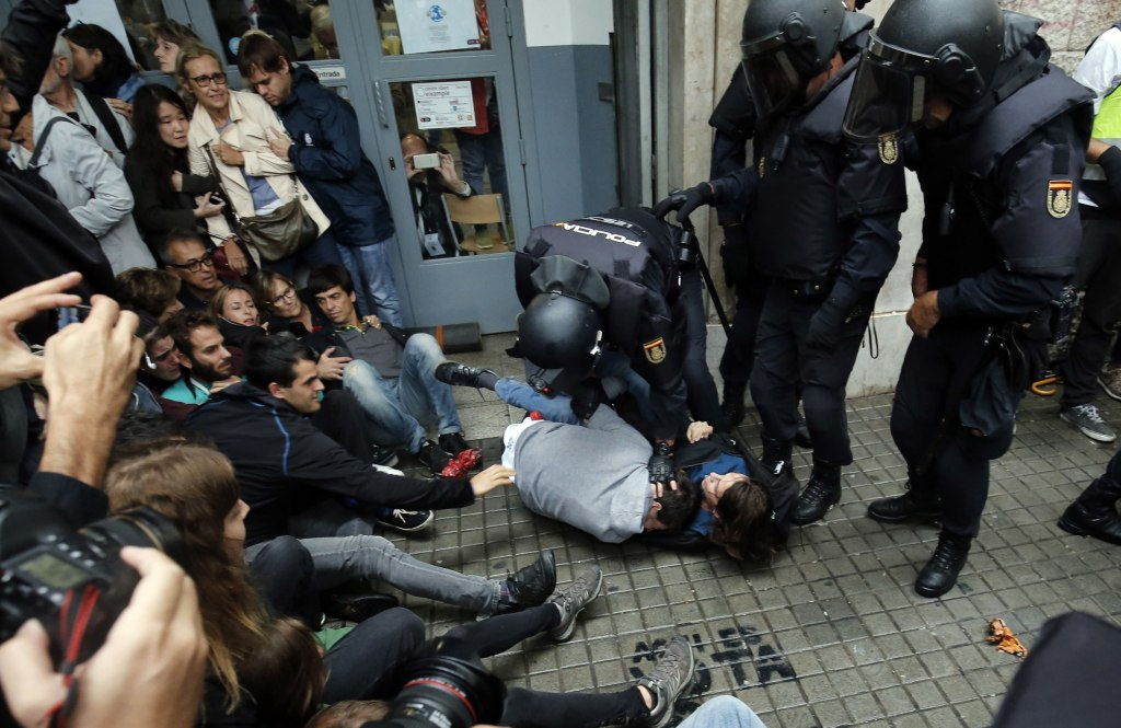 Image: Spanish police hold voters outside a polling station in Barcelona early Sunday as the Catalonia independence poll got underway.