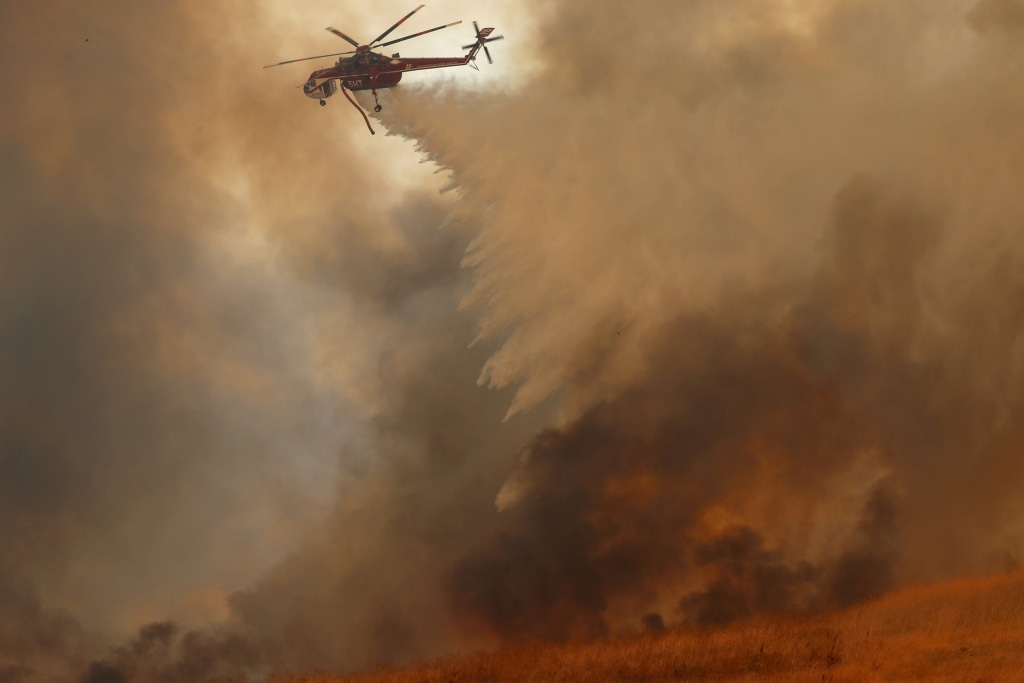 Image: A helicopter drops water on a wind-driven wildfire