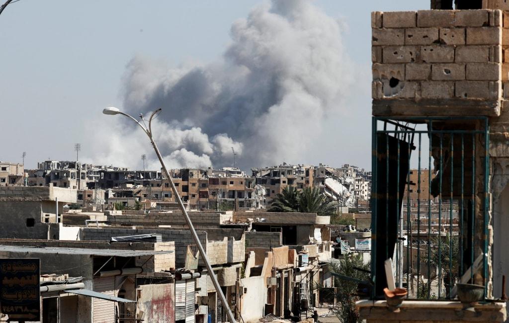 Image: Smoke rises near the sports stadium in Raqqa
