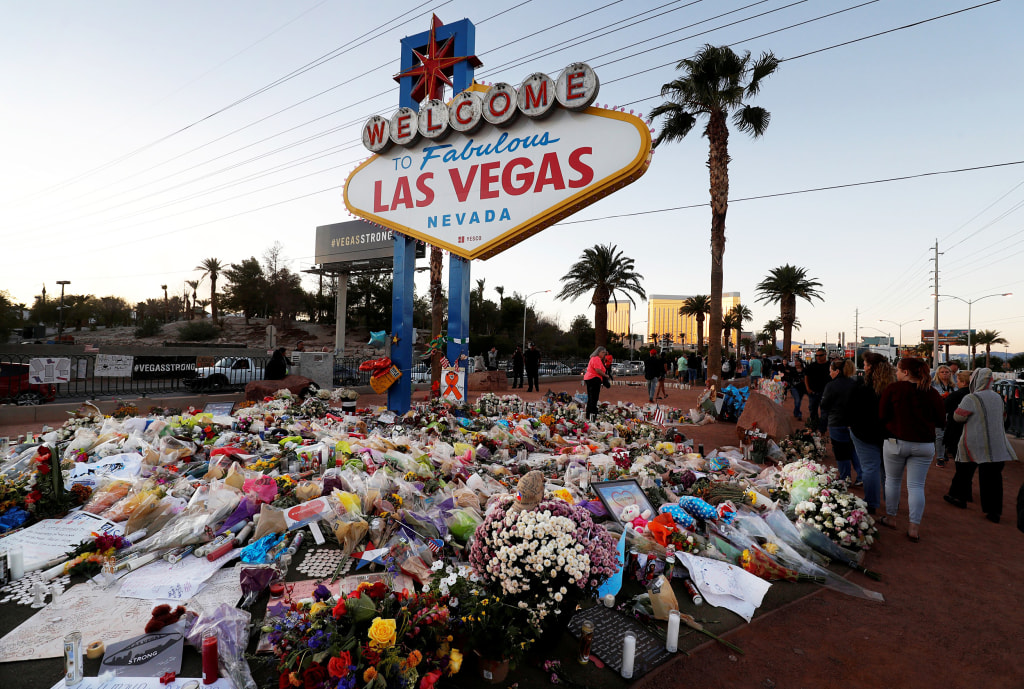 """Image: The """"Welcome to Las Vegas"""" sign is surrounded by flowers and items, left after the October 1 mass shooting, in Las Vegas"""