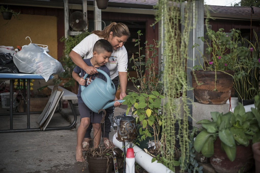 Image: Lidia Pena and her son water plants
