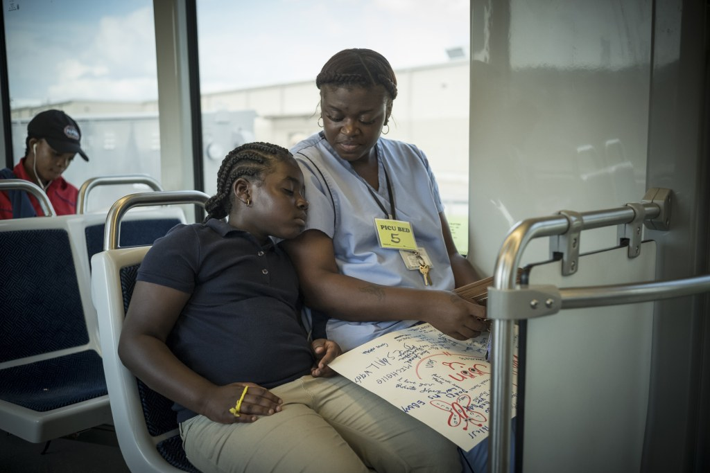 Image: Ebony Harrison and her daughter take the train to visit Harrison's infant daughter