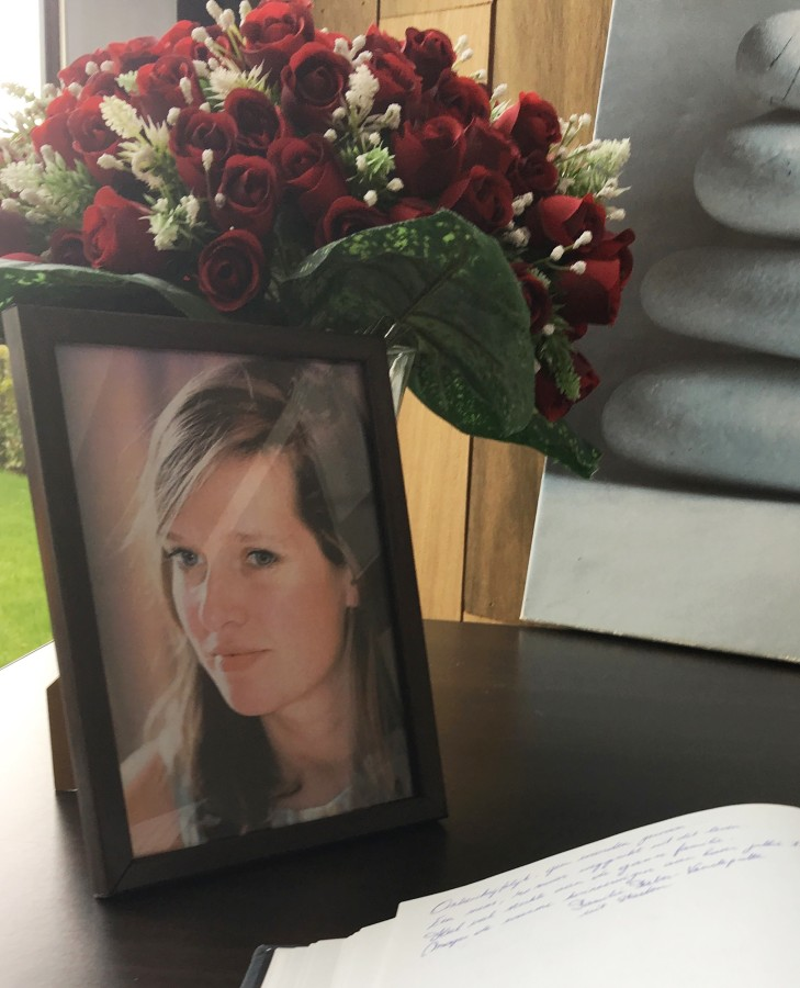 Image: A book of condolence is open next to a portrait of Ann-Laure Decadt in a community center in Staden, Belgium