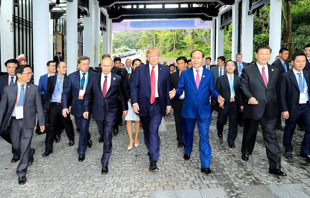Image: Presidents Trump and Putin walk together with Vietnamese President Tran Dai Quangat the APEC summit on Saturday