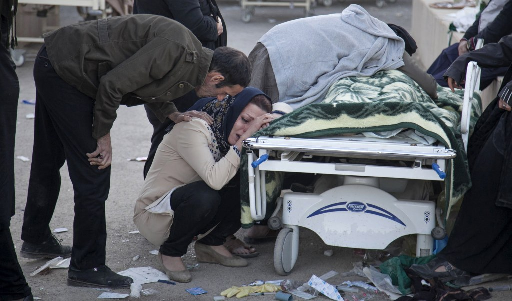 Image: Relatives weep over the body of an earthquake victim
