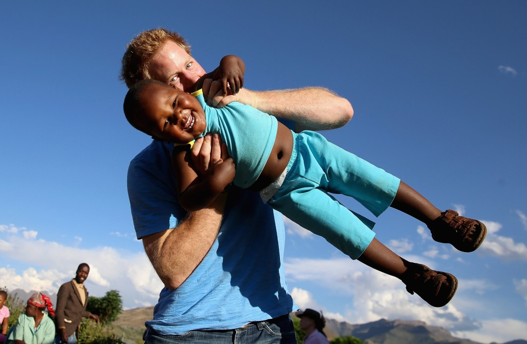 Image: Prince Harry swings a young three-year-old orphan boy in Lesotho, Africa.
