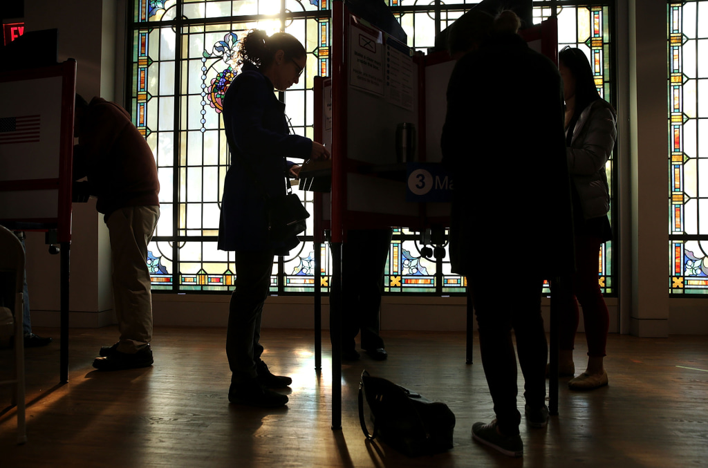 Image: Voters fill out their paper ballots in a polling place on election day