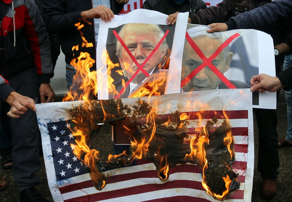 Image: Palestinians burn posters depicting Netanyahu and Trump during a protest against the U.S. intention to move its embassy to Jerusalem and to recognize the city of Jerusalem as the capital of Israel, in Rafah in the southern Gaza Strip