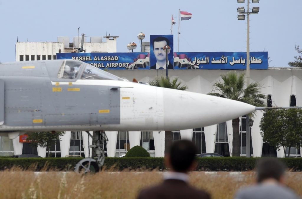 Image: A Russian Su-24 bomber passes by a portrait of Bashar al-Assad at Hemeimeem air base