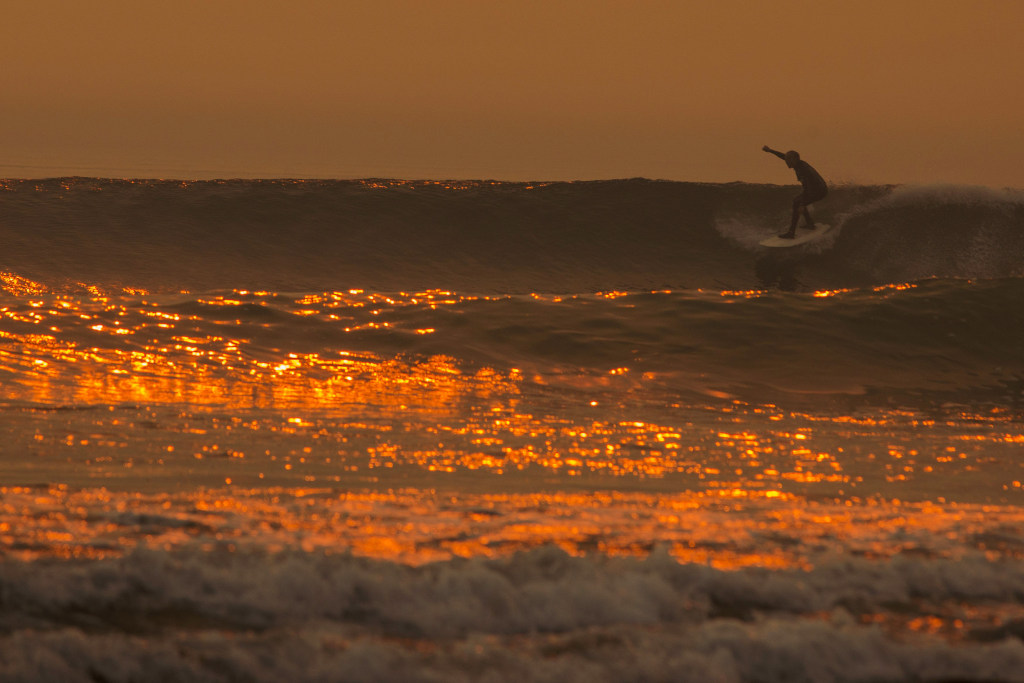 Image: A smoke-filled sky filters orange light around a surfer