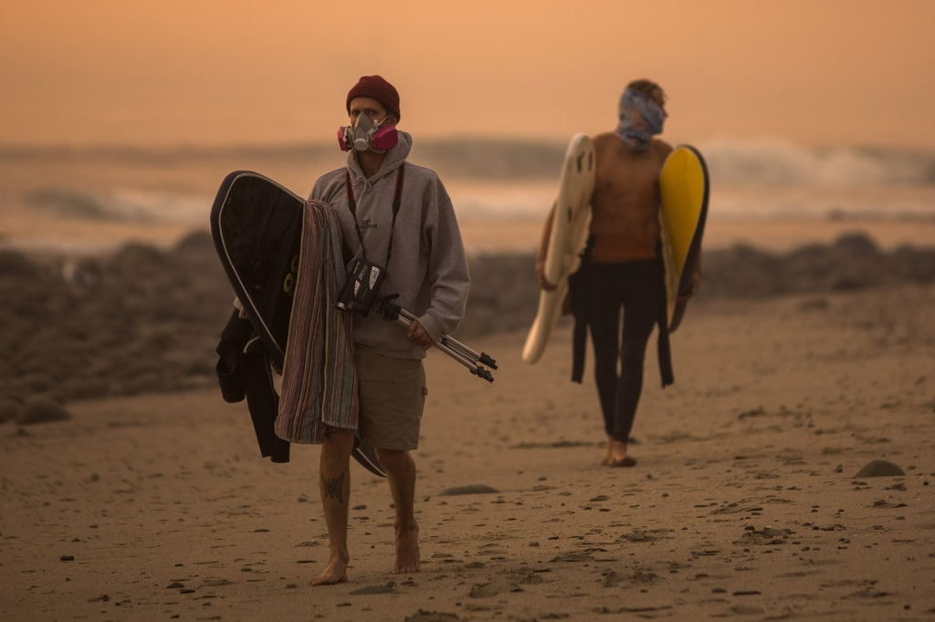 Image: A smoke-filled sky filters orange light around surfers
