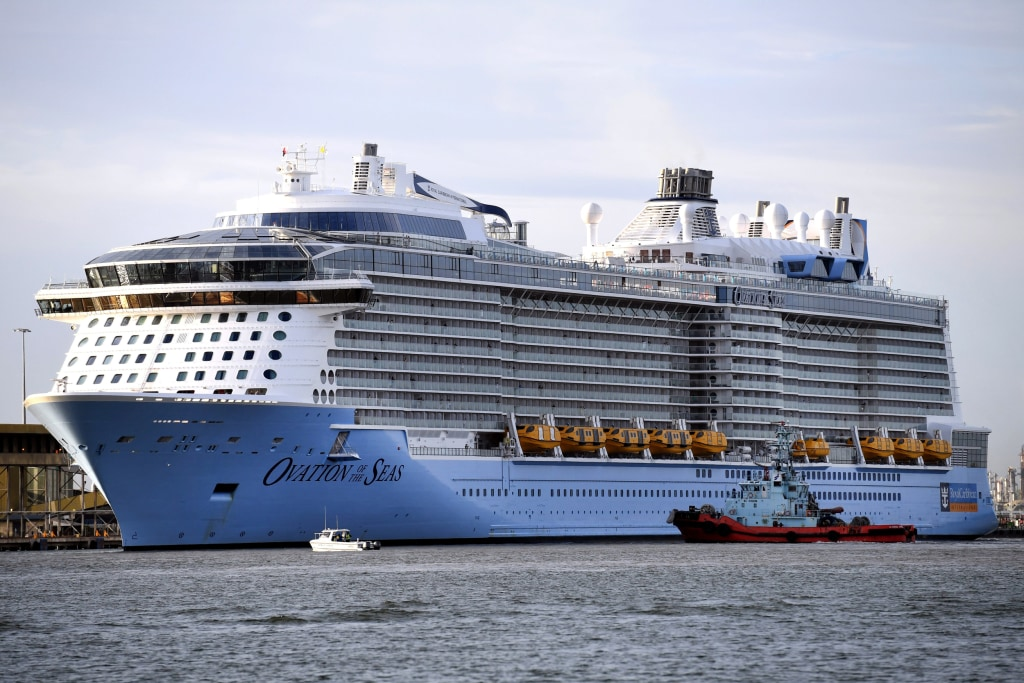 Image: A tugboat is dwarfed by Royal Caribbean cruise ship Ovation of the Seas as she docks at the Port of Brisbane, Australia, Feb. 22, 2017.