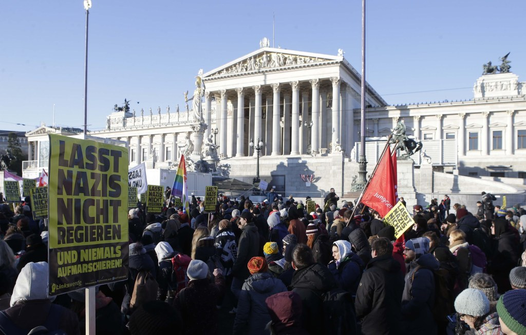 Image: Protesters hold banners in front Austria's parliament
