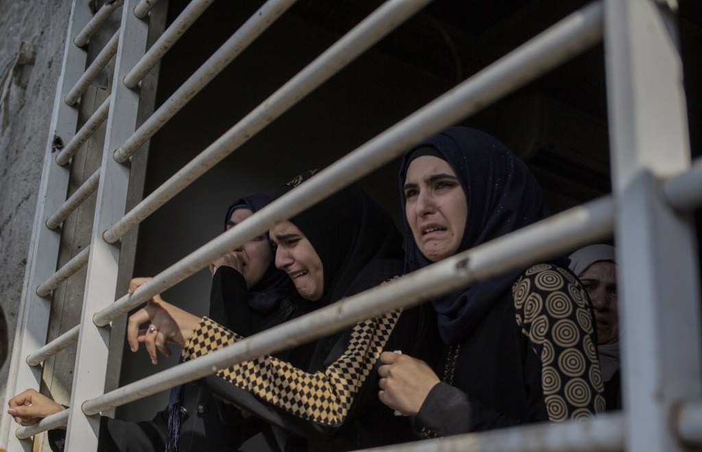 Image: A family disinters the body of a loved one from their garden in Mosul