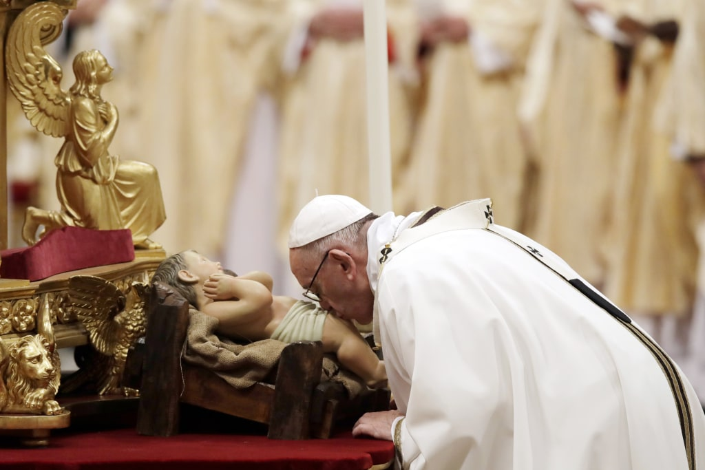Image: Pope Francis kisses a statue of baby Jesus as he celebrates the Christmas Eve Mass in St. Peter's Basilica at the Vatican