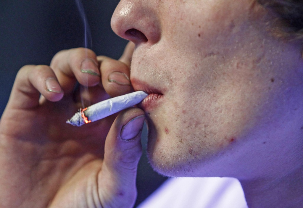 Image: Russell Diercks smokes a half marijuana and tobacco joint inside of Frankie Sports Bar and Grill in Olympia