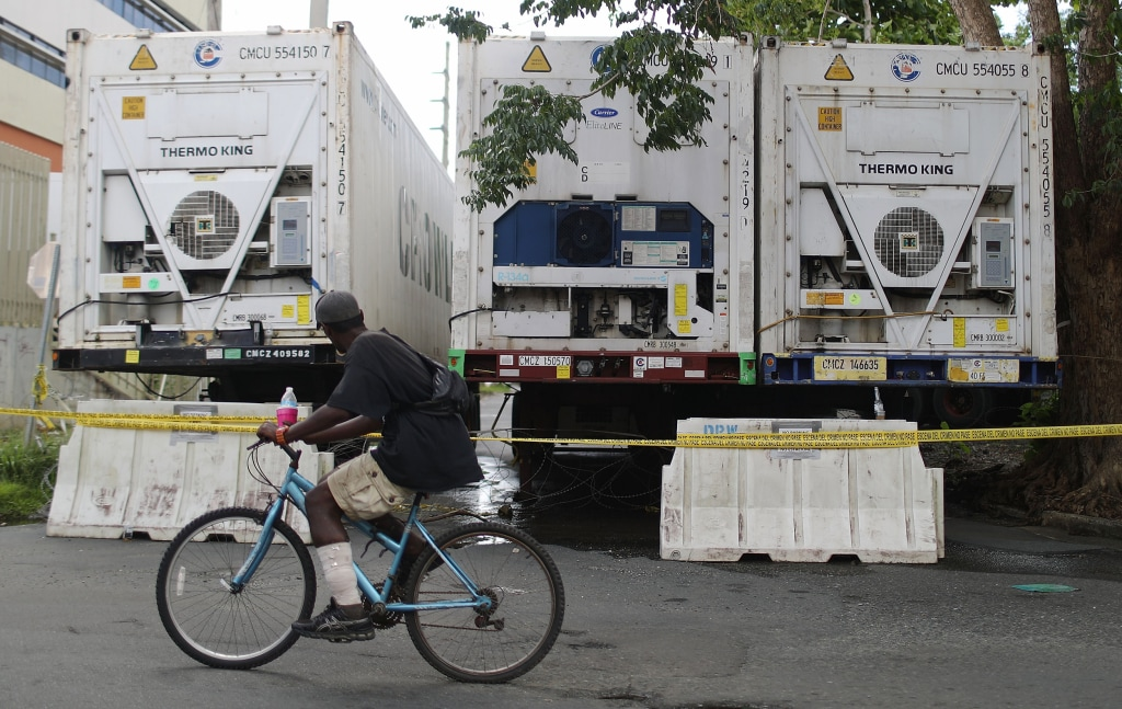 Image: A man bikes past refrigerated FEMA trailers
