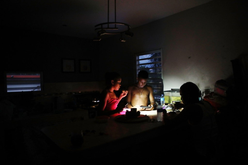 Image: Family members eat dinner at dusk with light from a cell phone