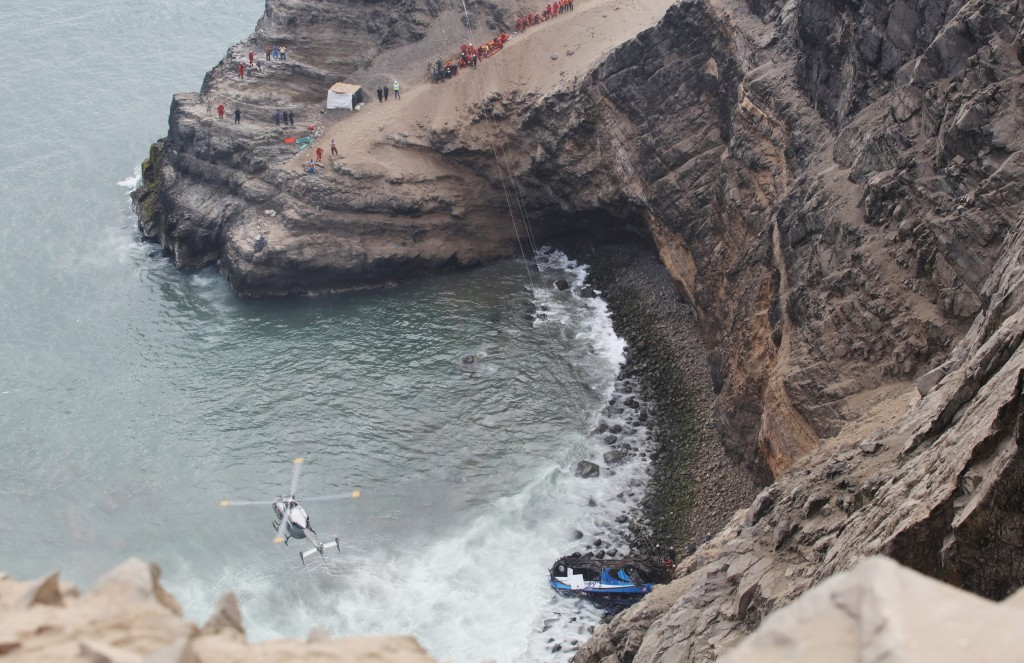 Image: A helicopter helps rescue workers at the scene after a bus crashed with a truck and careened off a cliff along a sharply curving highway north of Lima