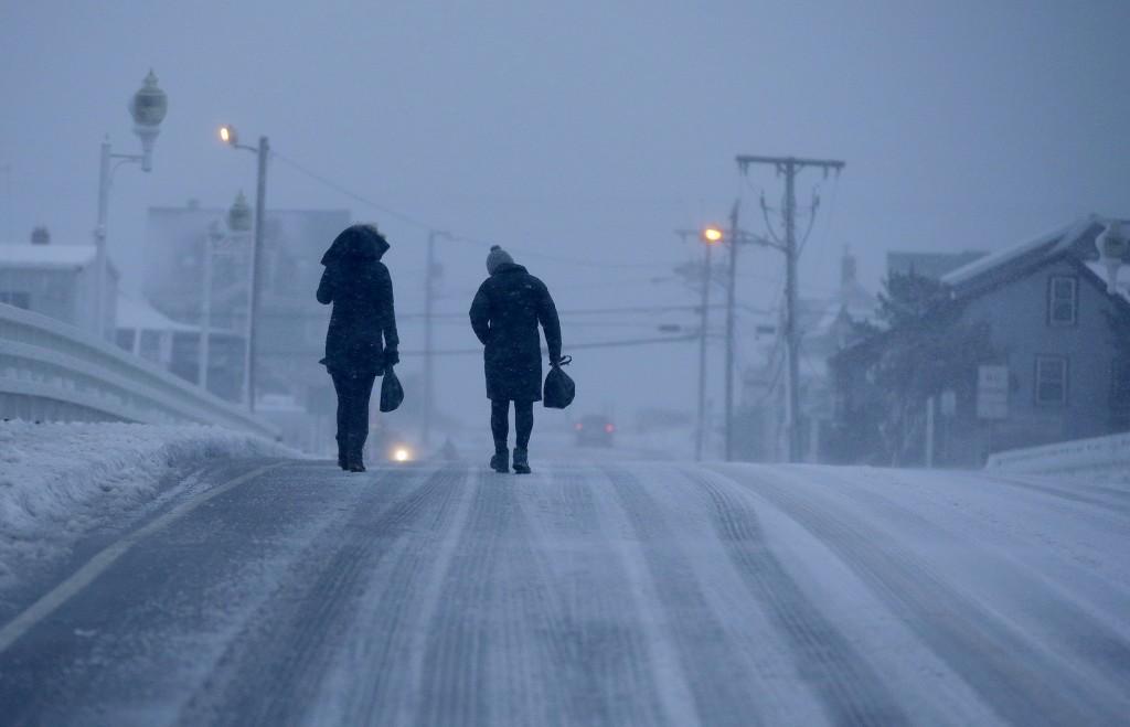 Image: Two people walk across the Humarock bridge as blizzard conditions begin to wind-down on Jan. 4, 2018, in Marshfield, Massachusetts.
