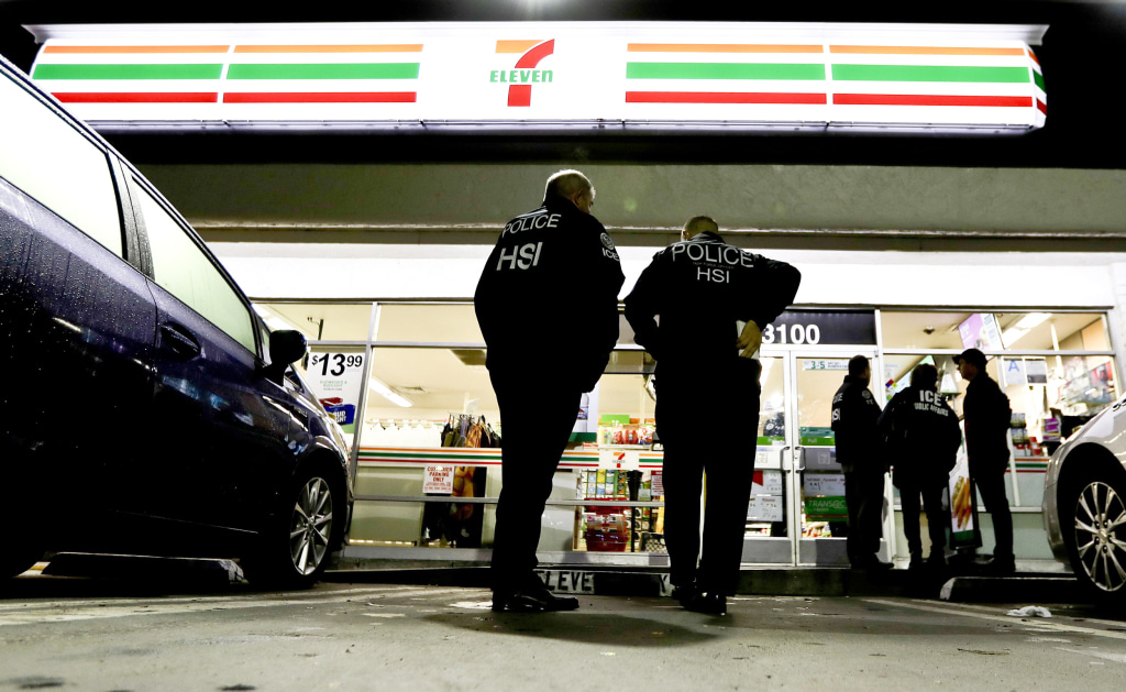 Image: U.S. Immigration and Customs Enforcement agents serve an employment audit notice at a 7-Eleven convenience store